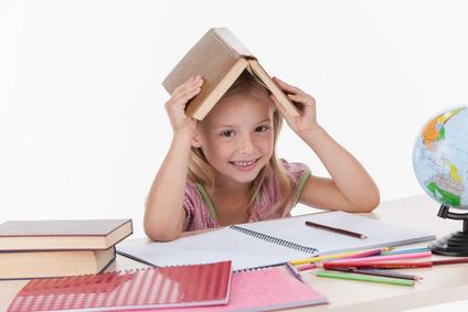 Mädchen welches gerade lernt und dabei Buch über dem Kopf hält